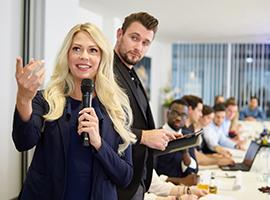 Eine blonde Frau moderiert eine Tagung in der HOGALOUNGE