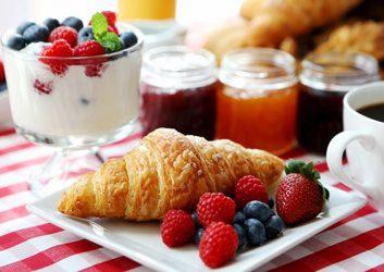 Ein Croissant mit Früchten neben einer Tasse Kaffee vor verschiedenen Marmeladengläsern und einem Glas mit Joghurt und Beeren