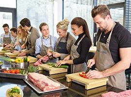 Mehrere Kochschüler mit Schürzen schneiden Gemüse und Fleisch in der HOGALOUNGE Kochschule