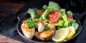 Mit Zitronen angerichteter Fisch auf Gemüse- und Kräuterbett