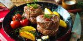 Zwei geschnürte Filet Steak Medaillons in der Pfanne mit Tomaten und Kartoffeln